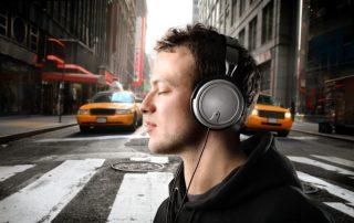 مردی که هدفون به گوش دارد از خیابان رد میشود